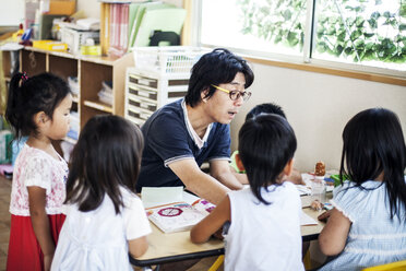 Male teacher talking to group of children at a table n a Japanese preschool. - MINF09631
