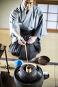 Traditional Japanese Tea Ceremony, man wearing kimono sitting on floor, using a Hishaku, a bamboo ladle, to pour hot water. - MINF09686