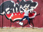 Happy mature woman jumping in the air in front of graffiti wall - LA02168