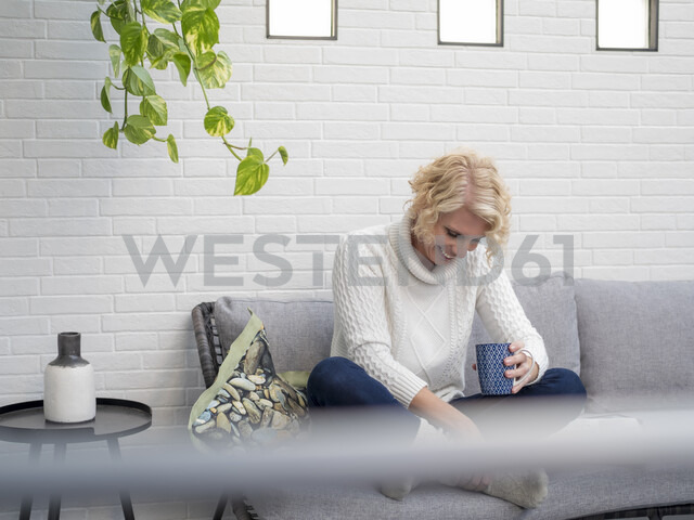 Smiling mature woman sitting on couch at home holding coffee mug - LAF02171