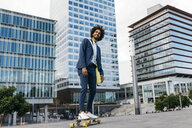Spain, Barcelona, young businessman riding skateboard in the city - JRFF02038