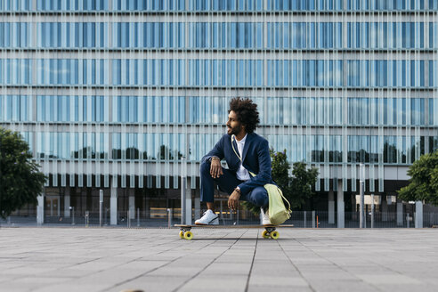 Spain, Barcelona, young businessman crouching on skateboard in the city - JRFF02041