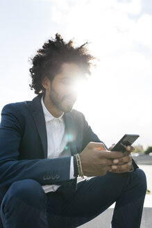 Young businessman sitting outdoors in sunshine using cell phone - JRFF02044