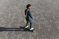 Young businessman riding skateboard on a square - JRFF02050