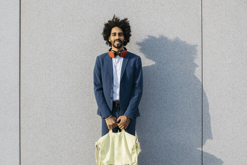 Portrait of smiling young businessman with bag and headphones at a wall - JRFF02056