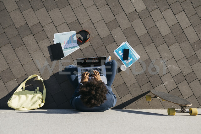 Young businessman sitting outdoors at a wall working on laptop - JRFF02062 - Josep Rovirosa/Westend61