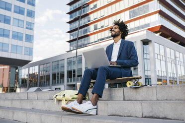 Spain, Barcelona, young businessman sitting outdoors in the city working on laptop - JRFF02065
