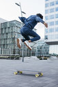 Spain, Barcelona, young businessman doing skateboard tricks in the city - JRFF02077