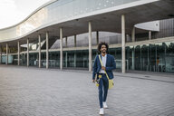 Spain, Barcelona, young businessman leaving office building holding skateboard in the city - JRFF02080