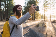 USA, North California, smiling bearded man taking a selfie in a forest near Lassen Volcanic National Park - KKAF02978