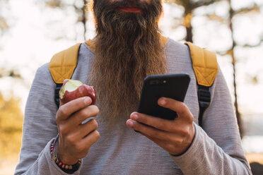 Close-up of bearded man using cell phone and eating an apple on a hiking trip in a forest - KKAF02984