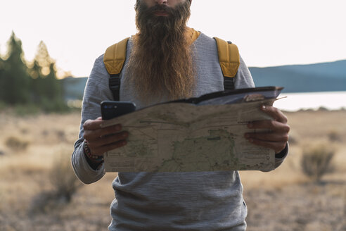USA, North California, close-up of bearded man using cell phone and map on a hiking trip near Lassen Volcanic National Park - KKAF02987