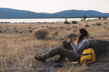 USA, North California, bearded young man using cell phone during a break on a hiking trip near Lassen Volcanic National Park - KKAF02990