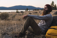 USA, North California, bearded young man having a break on a hiking trip near Lassen Volcanic National Park - KKAF02993