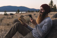 USA, North California, bearded young man with book and cell phone during a hiking trip near Lassen Volcanic National Park - KKAF02996