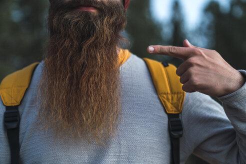 Close-up of man wearing backpack pointing at his beard - KKAF03005