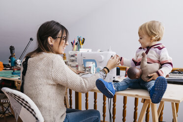 Happy mother with little daughter at home using sewing machine - JRFF02081