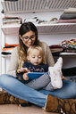 Happy mother and little daughter sitting on the floor at home using tablet - JRFF02099