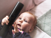 Baby girl holding remote control - LAF02183