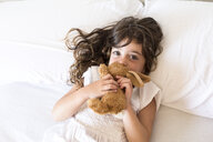 Little girl lying in bed with plush toy rabbit - ERRF00077