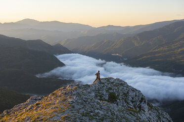 Italy, Umbria, Sibillini National Park, hiker on viewpoint at sunrise - LOMF00749