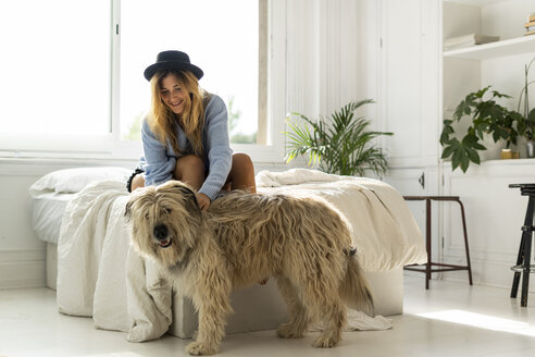 Smiling young woman sitting on bed stroking a dog - ERRF00084