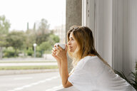 Young woman at the window holding cup of coffee - ERRF00090