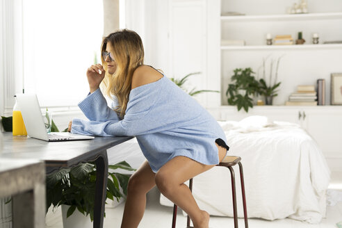 Young woman sitting in bedroom at home using laptop - ERRF00108