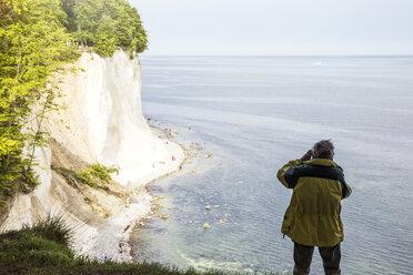 Germany, Mecklenburg-Western Pomerania, Ruegen, Jasmund National Park, chalk cliff, hiker photographing on viewpoint - MAMF00229