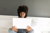 Happy woman sitting on bed looking at tablet - VABF01755