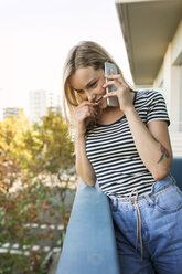 Smiling young woman talking on cell phone on balcony - VABF01761