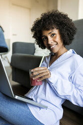 Portrait of smiling woman with soft drink sitting on floor using laptop - VABF01770
