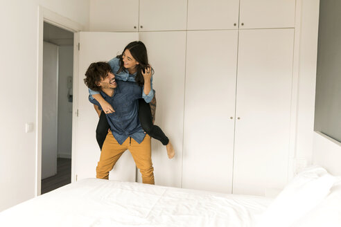 Cheerful man carrying girlfriend piggyback in bedroom at home - VABF01800
