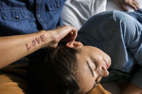 Tattooed man cuddling up with girlfriend - VABF01803