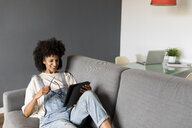 Smiling woman lying on couch at home using tablet - VABF01824