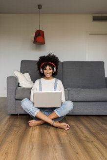 Portrait of smiling woman sitting at home with headphones and laptop - VABF01830