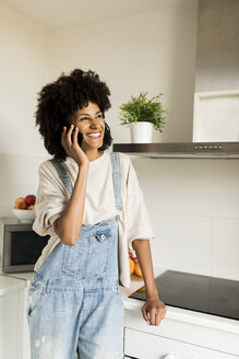 Happy woman on cell phone in kitchen at home - VABF01836