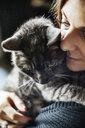 Woman hugging her grey tabby cat - JATF01067