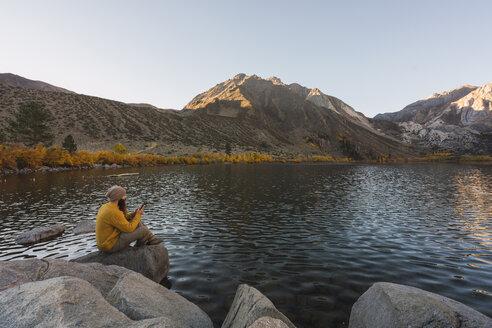 USA, California, Yosemite National Park, Mammoth lakes, hiker using smartphone at Convict Lake - KKAF03028