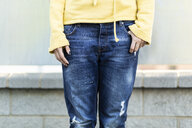 Young woman wearing old dark blue jeans, partial view - ERRF00110