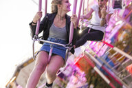 Mother and daughter having fun on chairoplane - FBAF00167