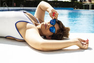 Portrait of plump young woman taking sunbath at swimming pool - ERRF00118
