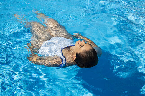 Young woman floating on water in swimming pool - ERRF00127