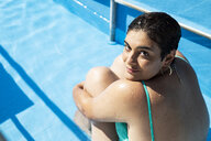 Portrait of content young woman relaxing in swimming pool - ERRF00133