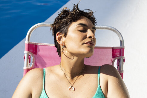 Portrait of young woman relaxing on sun lounger at swimming pool - ERRF00139