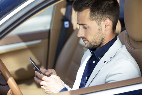 Young businessman sitting in car, using smartphone - JSRF00073