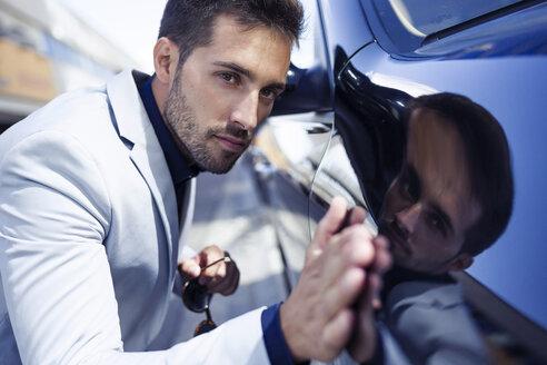 Young businessman stroking his polished car - JSRF00082