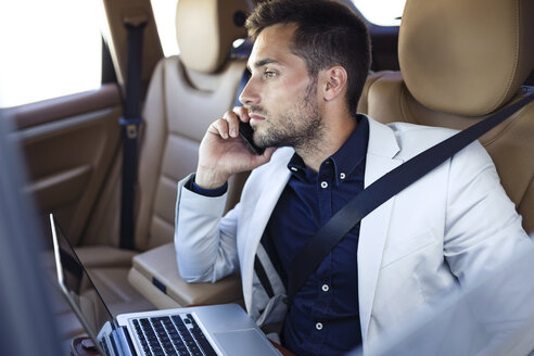 Young businessman working from the backseat of a car - JSRF00088