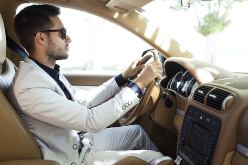Successful young businessman driving in his car - JSRF00091