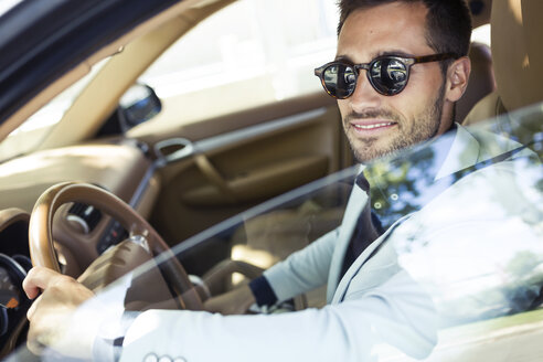 Successful young businessman driving in his car - JSRF00094